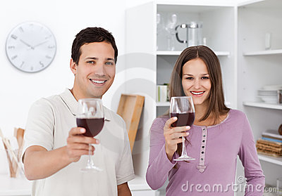 Young couple toasting with glasses of red wine