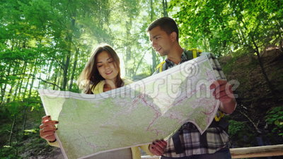 A young couple of tourists looking at a map. They stand in the rays of the sun in the forest near the waterfall. Adventures and an active way of life. 4K 10 stock video
