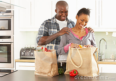 Young Couple Unpacking Shopping In Kitchen