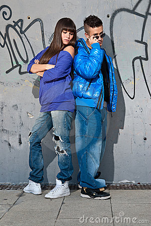 Young couple urban fashion standing portrait wall