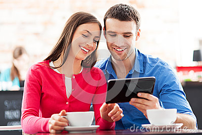 Couple using digital tablet in cafe