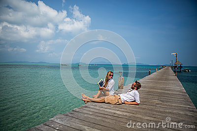 Young couple using digital tablet on wooden jetty