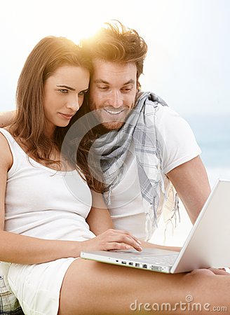 Young couple using laptop on the beach