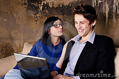 Young couple using laptop on couch