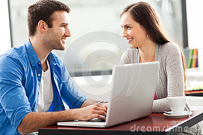 Couple talking and using laptop at cafe