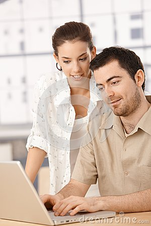 Young couple using laptop together at home smiling