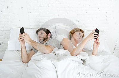 young couple using mobile phone in bed ignoring each other in relationship communication problems Stock Photo