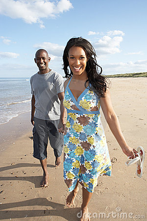 Young Couple Walking Along Shoreline
