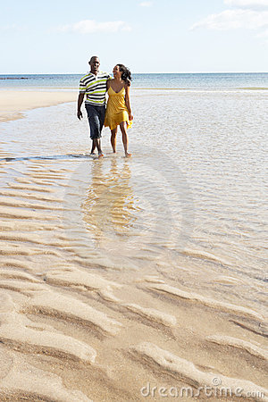 Young Couple Walking Along Shoreline Holding H