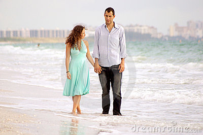 Young couple walking beach discussing problems