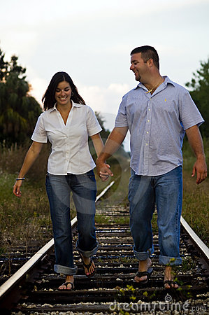 Young couple walking on rail tracks