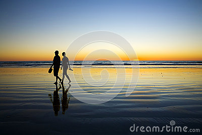Young Couple Walking on Romantic Beach at Sunset