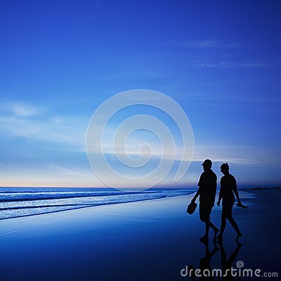 Young Couple Walking on Romantic Beach at Twilight