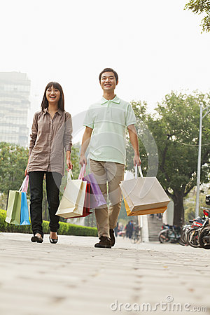 Young couple walking with shopping bags in hands, Beijing, China