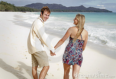 A young couple walks on the beach holding hands
