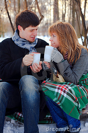 Young couple warming themselves in the winter park