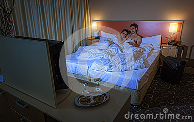Young couple watching TV in the hotel room at night