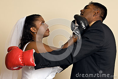 Young couple in wedding attire with boxing gloves
