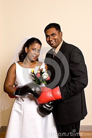Young couple in wedding attire wearing boxing gloves