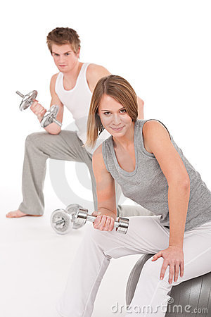 Young couple with weights and fitness ball