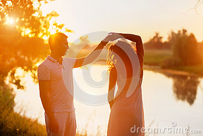 Young couple in white dancing on the background of sunset