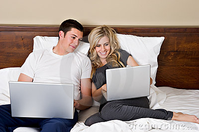 Young couple working on laptops in bed