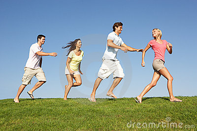 Young couples running through field
