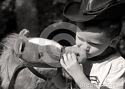 Young cowboy kissing his horse