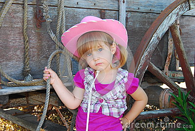 Young cowgirl next to wagon