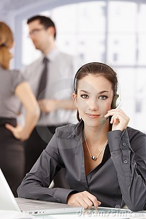 Young customer servicer using headphones in office