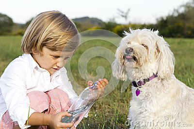 Young cute boy giving water to dog