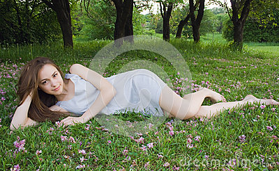 Young cute girl is leaning on the green grass