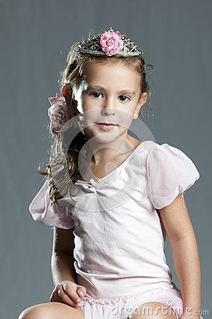 Young cute girl princess against grey background