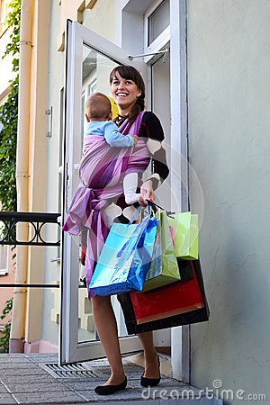 Young cute mother with baby in sling