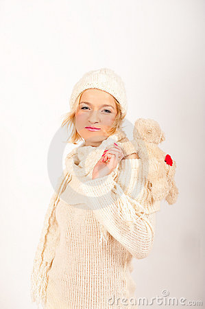 Young cute winter girl in knit hat with toy