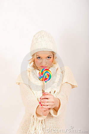 Young cute winter girl with lollipop candy