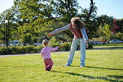 Young dad and his little daughter playing frisbee