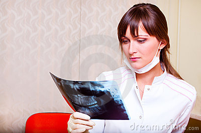 Young dentist looking at x-ray picture