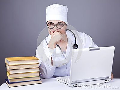 Young doctor with books and computer.