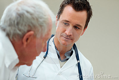 Young doctor conversing with an elderly patient