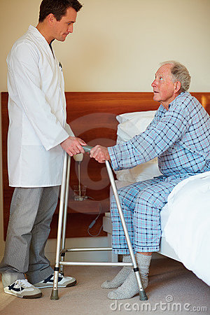 Young doctor helping an elderly patient