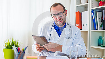Young doctor using tablet in his  surgery.
