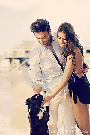 Young dream couple caressing dog at summer beach