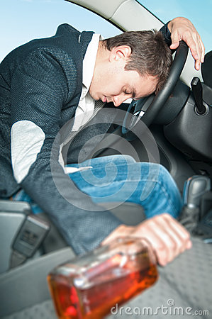 Young drunk driver sleeps in the car with bottle.