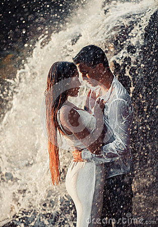 Free Young Enamored Couple Hugs Under Spray Of Waterfall. Royalty Free Stock Photography - 98187147