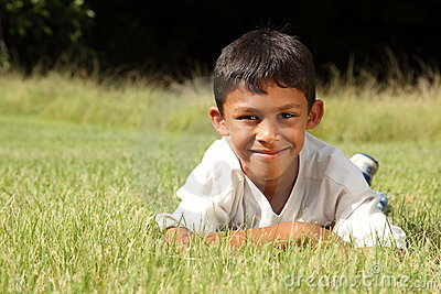 Young ethnic boy lying on the grass in park