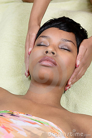 Young ethnic woman receiving reiki healing