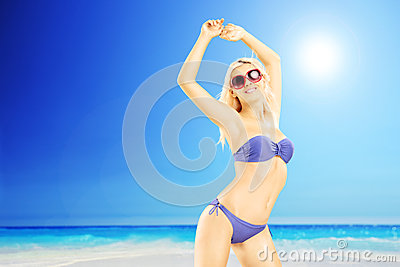 Young excited female in bikini enjoying on a sunny day