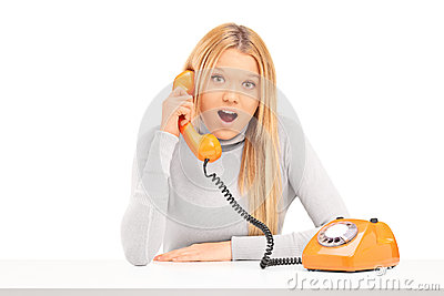 Young excited woman talking on a telephone