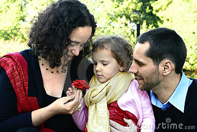Young family admiring a rose